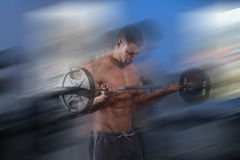 Man In The Gym Exercising Biceps With Barbell. Young Athlete Doing Heavy Weight Exercise For Biceps With Barbell - On A Blue Background Stock Images
