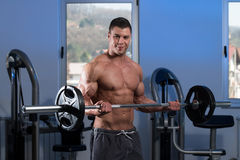 Man In The Gym Exercising Biceps With Barbell. Young Athlete Doing Heavy Weight Exercise For Biceps With Barbell - On A Blue Background Stock Image