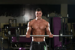 Man In The Gym Exercising Biceps With Barbell. Young Athlete In The Gym Performing Biceps Curls With A Barbell Royalty Free Stock Photography