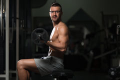 Man In The Gym Exercising Biceps With Barbell. Young Geek Athlete In The Gym Performing Biceps Curls With A Barbell Royalty Free Stock Image