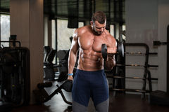 Man In The Gym Exercising Biceps With Dumbbells. Young Athlete In The Gym Performing Biceps Curls With A Dumbbells Royalty Free Stock Images