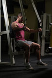 Man In The Gym Exercising Chest On Machine Stock Photo