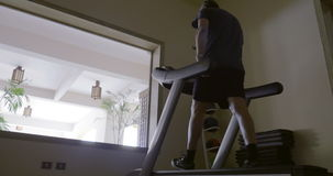 Man in the gym exercising on treadmill. Steadicam low angle shot of a mature man exercising on treadmill working on low speed. Gym in the hotel with view on the stock video footage