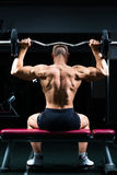 Man in gym or fitness studio on weight bench Stock Photo