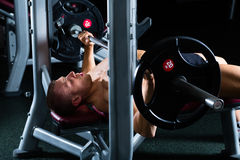 Man in gym or fitness studio on weight bench Royalty Free Stock Photography