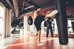 Man at the gym. Handsome muscular man in boxing gloves is practicing with a punching bag while warming up in gym Stock Photos