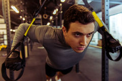 Man in gym. Handsome young muscled man training with trx while working out in gym Royalty Free Stock Images