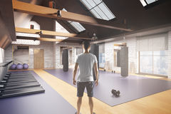 Man in gym interior. Back view of young man in creative new gym interior with equipment, city view and daylight. 3D Rendering. Fitness concept Royalty Free Stock Images