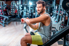 Man in the gym. Lifestyle portrait of handsome muscular man looking at the smart watch in the gym Stock Image