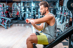 Man in the gym. Lifestyle portrait of handsome muscular man looking at the smart watch in the gym Royalty Free Stock Photos