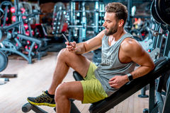 Man in the gym. Lifestyle portrait of handsome muscular man with phone sitting on the simulator in the gym Stock Images