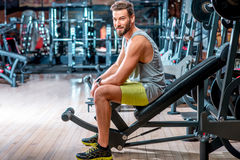 Man in the gym. Lifestyle portrait of handsome muscular man sitting on the simulator in the gym Stock Images