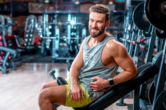 Man in the gym. Lifestyle portrait of handsome muscular man sitting on the simulator in the gym Royalty Free Stock Photos