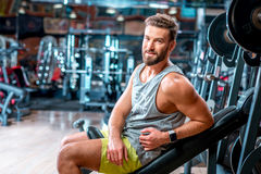 Man in the gym. Lifestyle portrait of handsome muscular man sitting on the simulator in the gym Royalty Free Stock Image