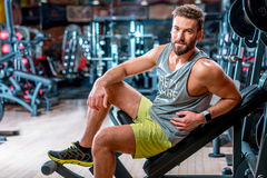 Man in the gym. Lifestyle portrait of handsome muscular man sitting on the simulator in the gym Royalty Free Stock Photo