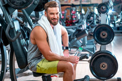 Man in the gym. Lifestyle portrait of handsome muscular man with towel sitting on the simulator in the gym Royalty Free Stock Photography