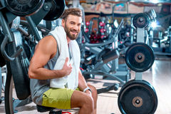 Man in the gym. Lifestyle portrait of handsome muscular man with towel sitting on the simulator in the gym Royalty Free Stock Images