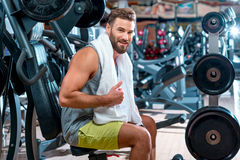 Man in the gym. Lifestyle portrait of handsome muscular man with towel sitting on the simulator in the gym Stock Photography