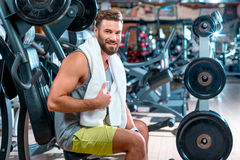 Man in the gym. Lifestyle portrait of handsome muscular man with towel sitting on the simulator in the gym Stock Photo