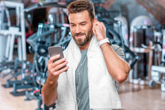 Man in the gym. Lifestyle portrait of handsome smiling man standing with mobile phone after the training in the sport gym Stock Image