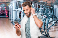 Man in the gym. Lifestyle portrait of handsome smiling man standing with mobile phone after the training in the sport gym Royalty Free Stock Photo
