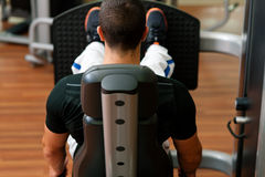 Man in gym on machine exercising Royalty Free Stock Images