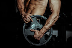 Man in gym. Muscular bodybuilder guy doing exercises with barbell. Strong person with Tense male hand with veins barbell. Modern journal toning Stock Photo