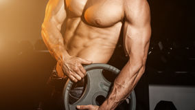 Man in gym. Muscular bodybuilder guy doing exercises with barbell. Strong person with Tense male hand with veins barbell. Modern journal toning. Flare for text Royalty Free Stock Photo