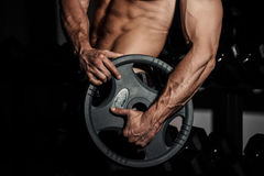 Man in gym. Muscular bodybuilder guy doing exercises with barbell. Strong person with Tense strong male hand with veins. Barbell Stock Photos