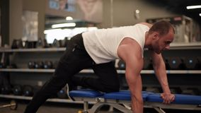 Man on the gym. Muscular men lifting weights on the bench stock video footage