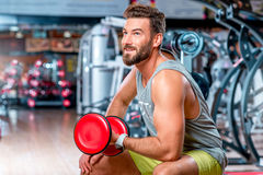Man in the gym. Muscular man training with red dumbbell in the gym Royalty Free Stock Photography