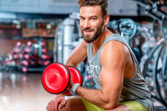 Man in the gym. Muscular man training with red dumbbell in the gym Royalty Free Stock Image