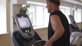Man in the gym runs on a treadmill. Side view stock video