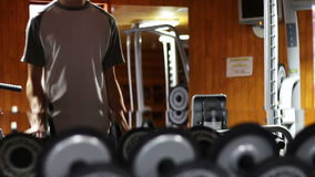 The man in the gym shakes his biceps using weights stock video