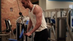 Man on the gym. Man stretching on exercise equipment stock video footage