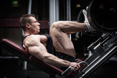 Man in gym training at leg press. To define his upper leg muscles Stock Photos