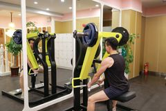 Asian chinese man in gym lifting weights. Man in gym try with dumbbells Royalty Free Stock Photos