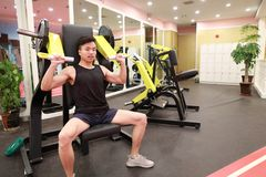 Asian chinese man in gym lifting weights. Man in gym try with dumbbells Royalty Free Stock Photography