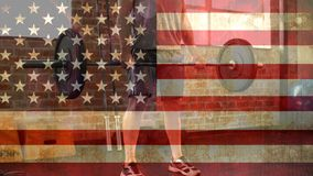 Man at the gym video. Man lifting weights at the gym against american flag background stock video