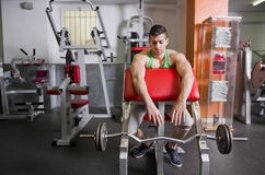 Man in gym with weights bar Stock Image