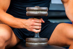 Man in gym workout with fitness equipment. Man holding dumbbell workout at gym. Royalty Free Stock Photo