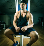 Man in gym. Young adult man is sitting in gym Stock Images