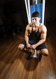 Man in gym. Young adult man is sitting in gym Royalty Free Stock Image