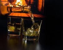 Man hällande exponeringsglas av whisky med iskuber framme av spisen Arkivbild