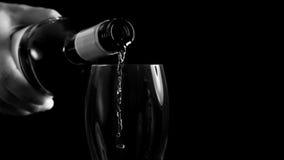 Man hällande vitt vin in i ett exponeringsglas Arkivbild