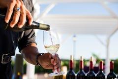 Man hällande vitt vin in i ett exponeringsglas royaltyfria bilder