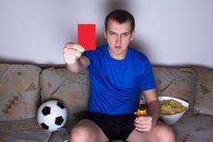 Man hållande ögonen på fotboll på tv och uppvisning av det röda kortet Arkivfoto