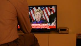 Man hållande ögonen på TV efter USA-val som lyssnar till Hillary Clinton anförande lager videofilmer