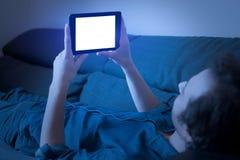 Man hållande ögonen på TV-serie på tryckning med den digitala minnestavlan arkivfoto