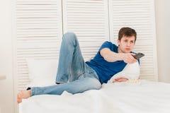 Man hållande ögonen på TVsammanträde på sängen som äter popcorn Royaltyfri Bild